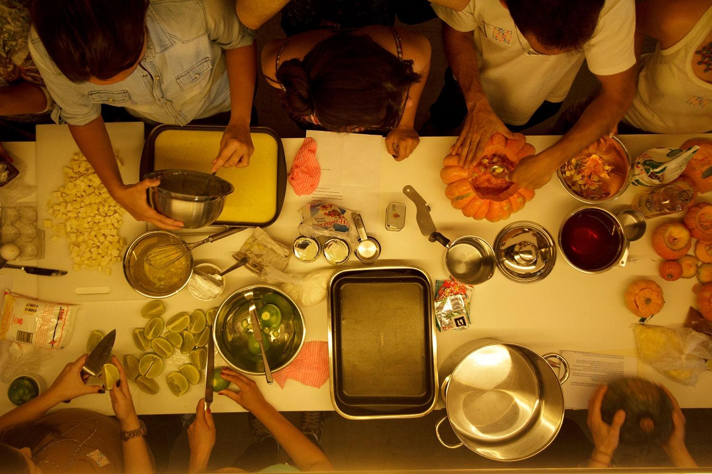 Mesa vista de cima, com pessoas cozinhando juntas, na inauguração da Cozinha Escola Nestlé, projeto do escritório de arquitetura Rosenbaum. Foto: Gabriel Cabral